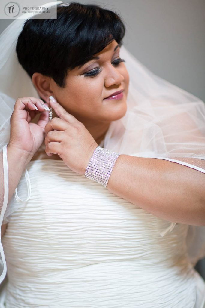 Bride fixing earring before wedding