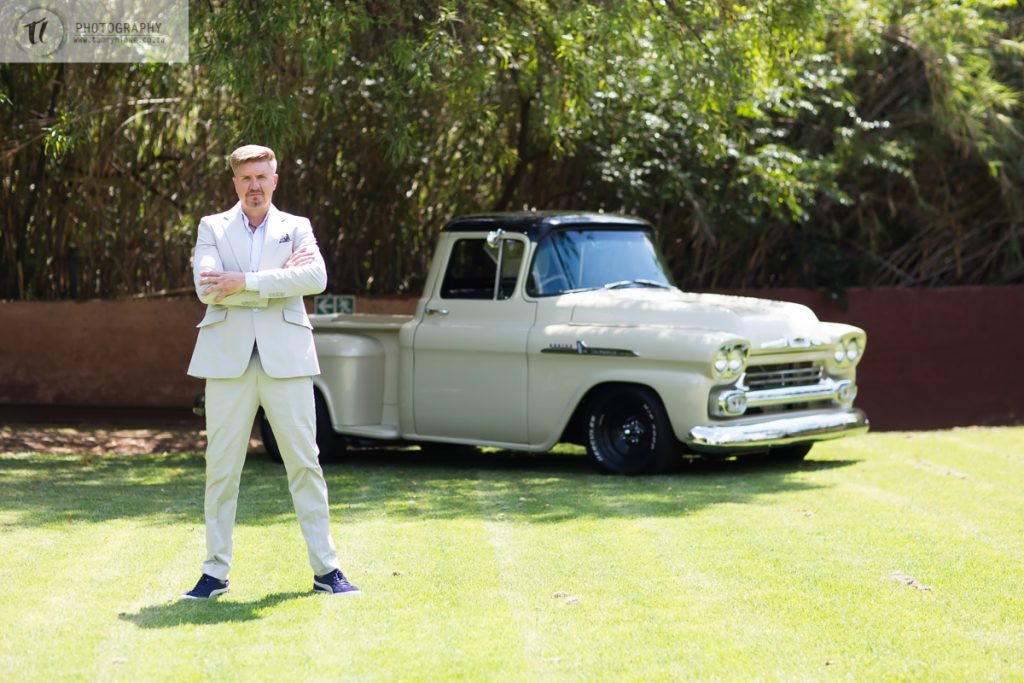 Groom standing with his vintage car