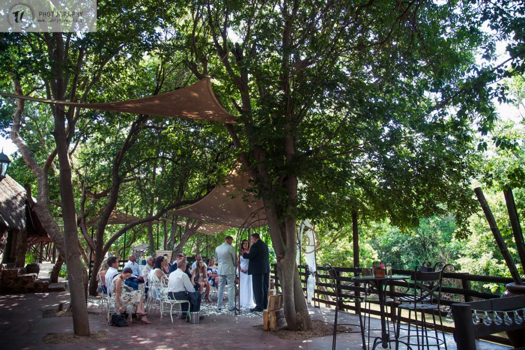 Bride & Groom saying vows under trees