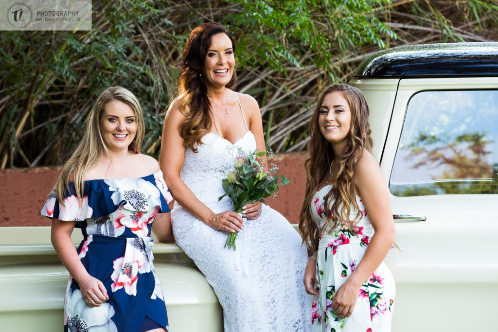 Bride with Bridesmaids sitting on vintage car