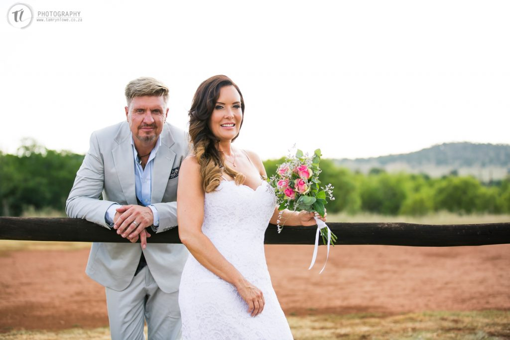 Bride & Groom leaning on rustic fence