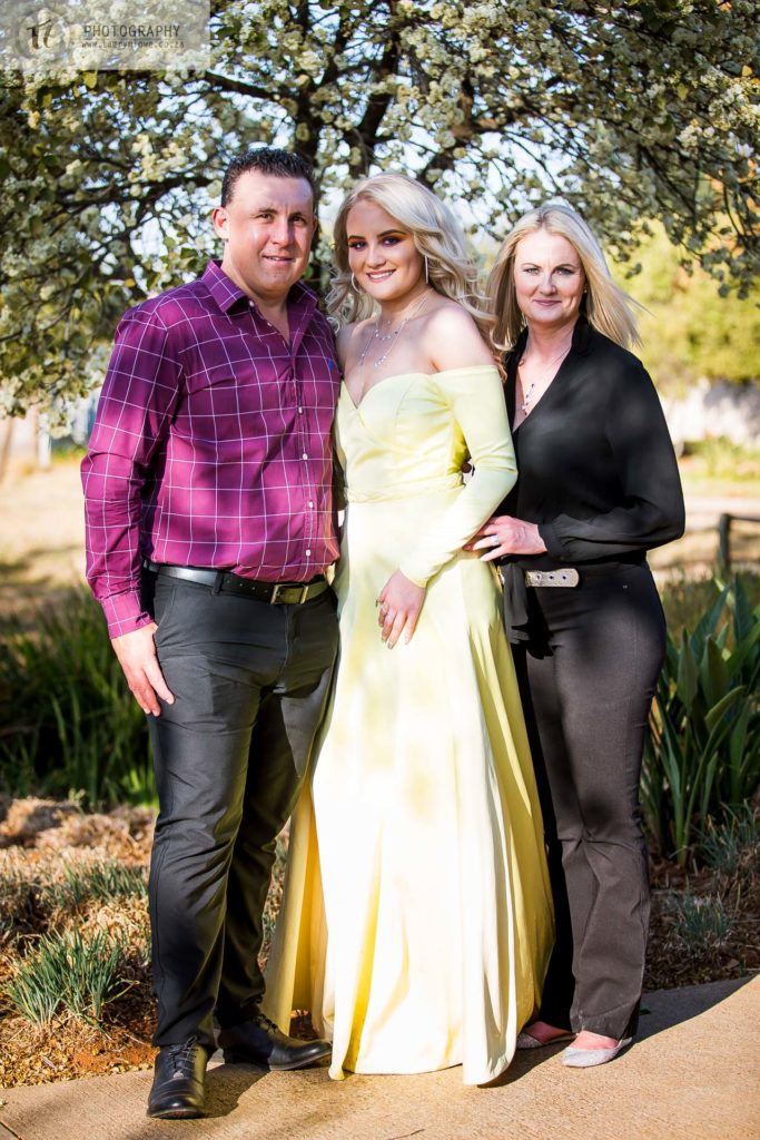 Young lady in formal attire with her mom and dad